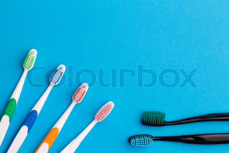 Stock image of 'Four multicolored and two black toothbrushes on empty blue background, place for words'