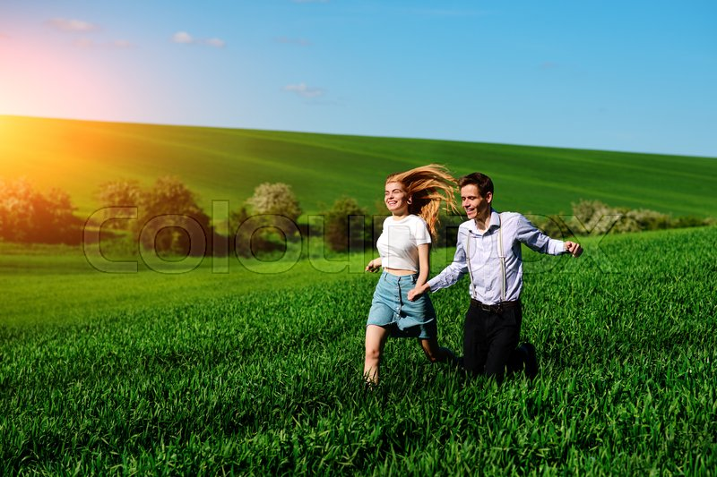 Stock image of 'Young happy lovers running on meadow with green grass and blue sky.'