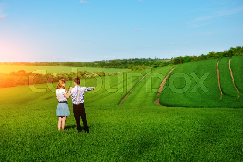Stock image of 'A young couple standing in the field, the girl shows her hand to the sky.'