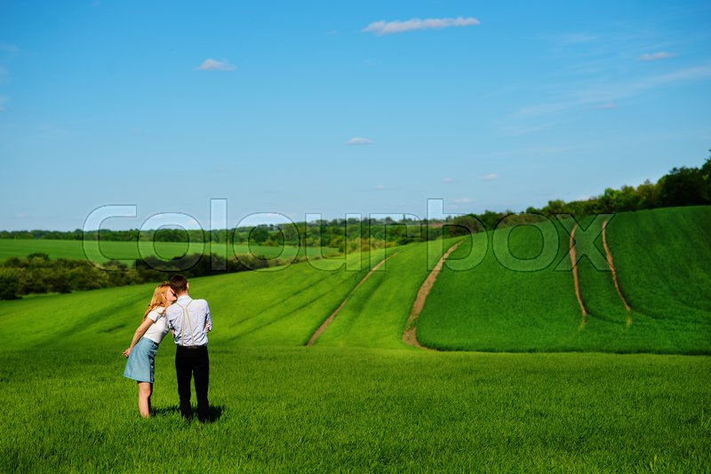 Stock image of 'A young couple standing in the field, the girl kisses the boy in the cheek.'