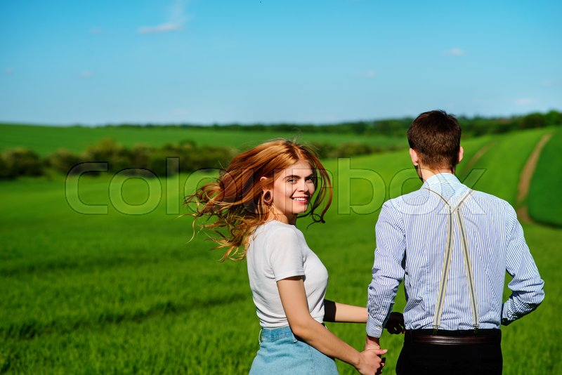 Stock image of 'Young couple running along a green field on a lovely sunny day.'