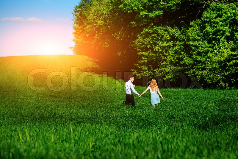 Stock image of 'Young happy lovers running on meadow with green grass and blue sky, From the back.'