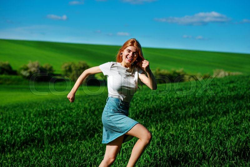 Stock image of 'Young beautiful woman running on a green field.'