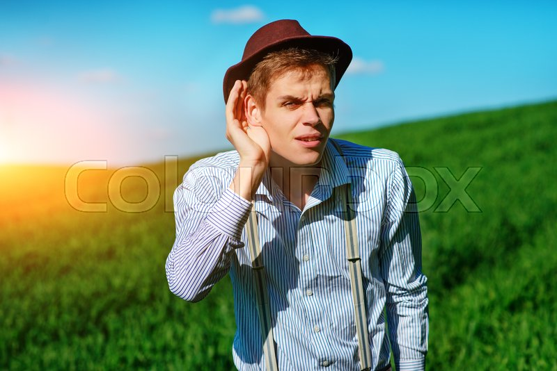 Stock image of 'Handsome man in the nature tries to hear something with putting his hand to his ears.'