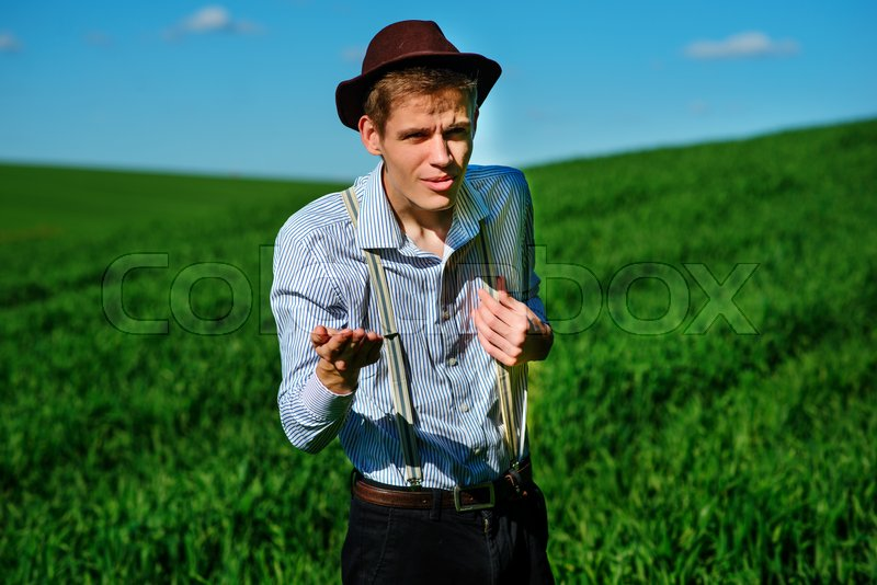 Stock image of 'Handsome man in the nature asking for something by stretching out his hand or can not understans.'