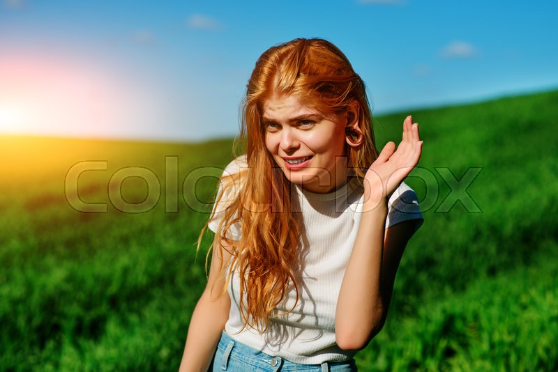 Stock image of 'Beautiful woman in the nature tries to understand somebody by trying to hear something with putting her hand to her ears.'