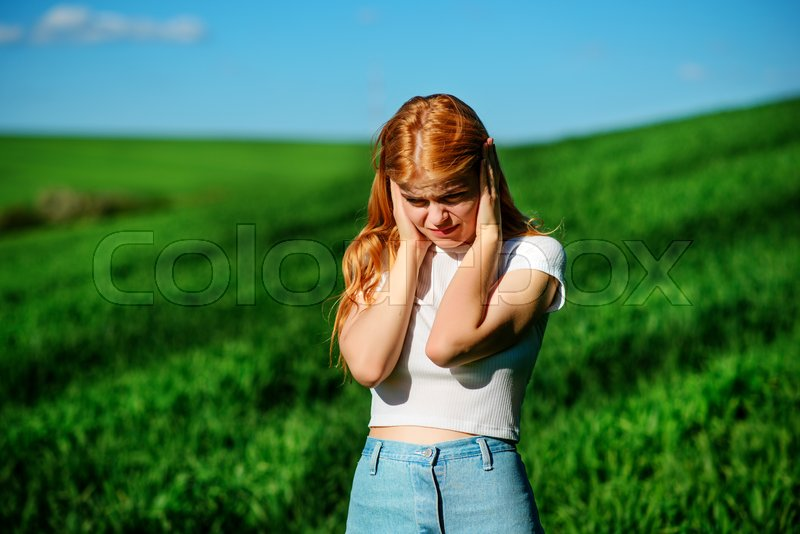 Stock image of 'Beautiful woman in the field is closing her ears with her hands:trying to ignore, not to hear something.'