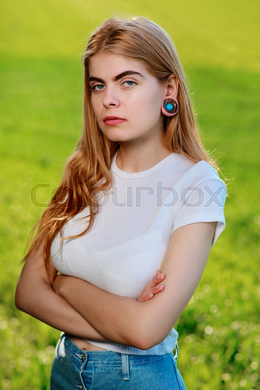 Stock image of 'Portrait of a young beautiful woman with wooden tunnels in her ears.'