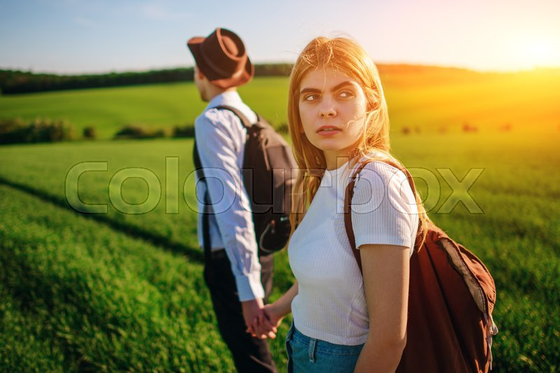 Stock image of 'A pair of lovers are holdings their hands together on a green field. Attractive man and a beautiful woman are walking between meadow.'