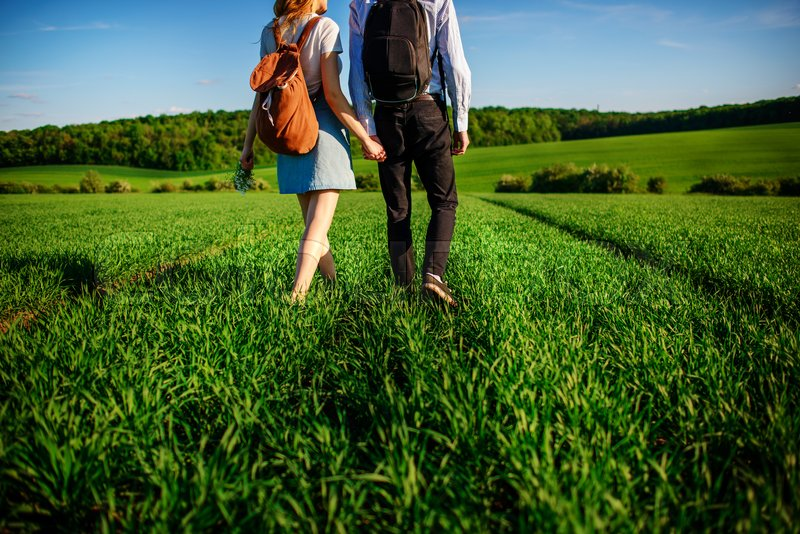 Stock image of 'Young couple is strolling through the greenfield. Woman and man are holding each other by the hands.'