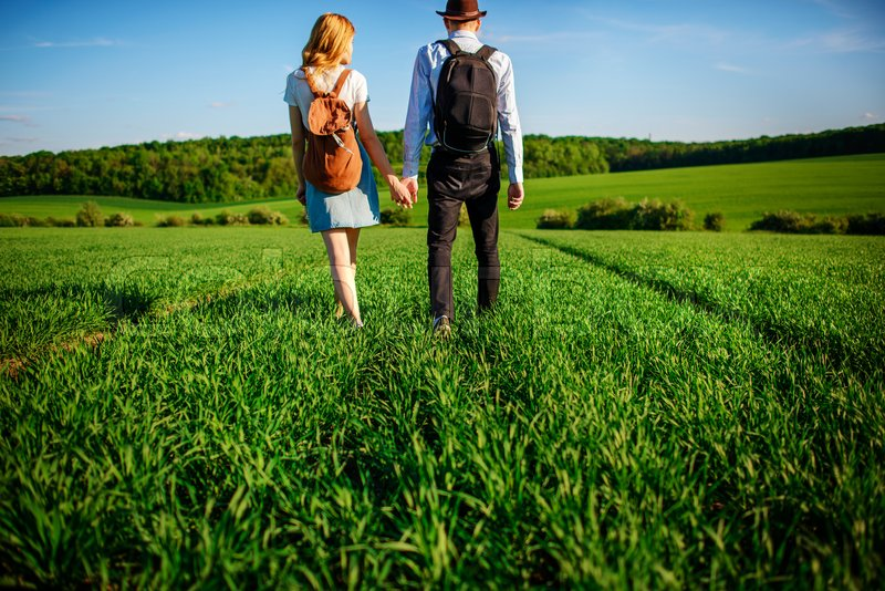 Stock image of 'With a backpack, a man in a hat and a woman with long hair go along the path. A couple walks along the meadow.'