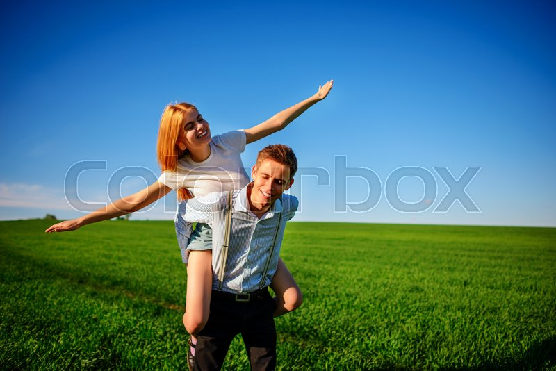 Stock image of 'Smiling Man is holding on his back happy woman, who pulls out her arms and simulates a flight against the background of the blue sky and the green field.'