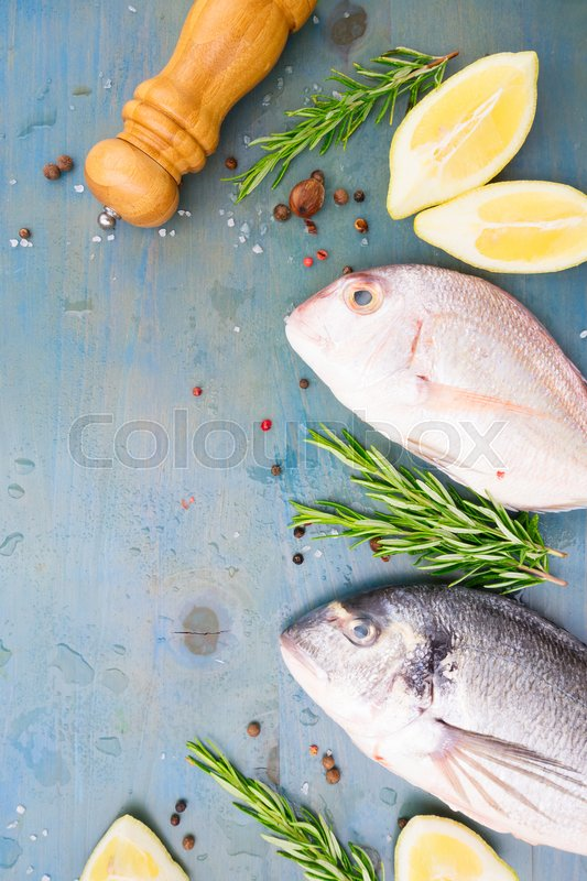 Stock image of 'fresh sea fish preparation - dorada breams with lemon and spices on blue wooden background'