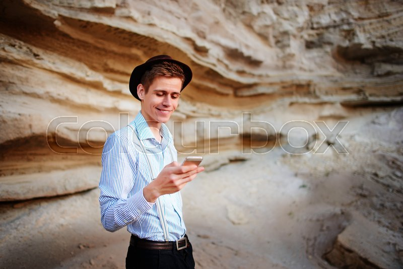 Stock image of 'An attractive man looking at the screen of a smartphone on the background of a sand quarry.'