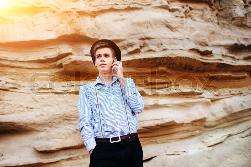 Stock image of 'Attractive man is standing in the middle of a sand quarry and making a call from a smartphone.'