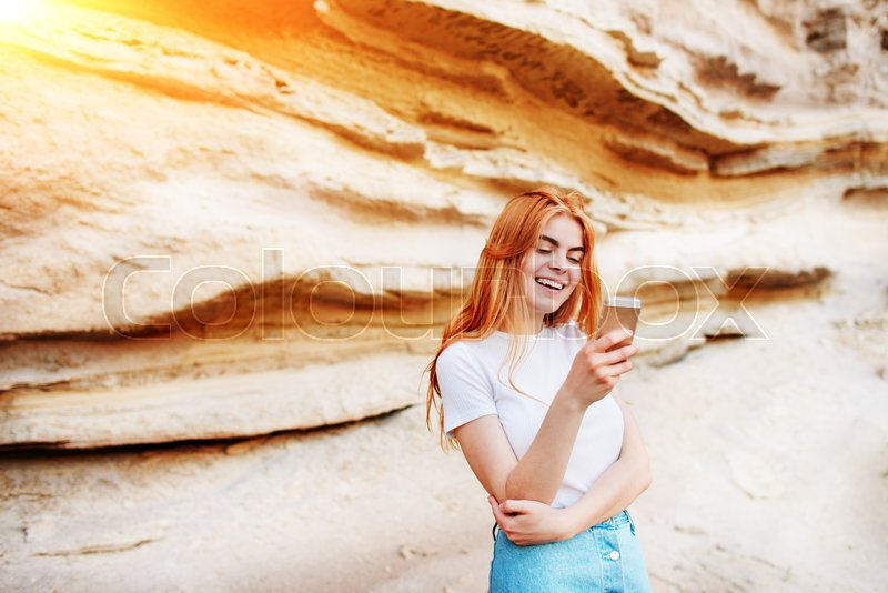 Stock image of 'Beautiful woman smiling and looking at the screen of a smartphone on the background of a sand quarry.'