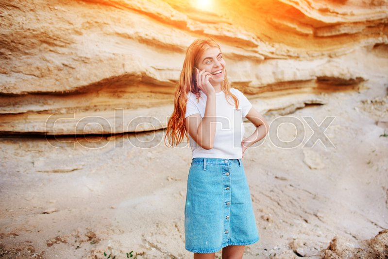 Stock image of 'A beautiful woman is smiling and talking by smartphone on the background of a sand quarry.'