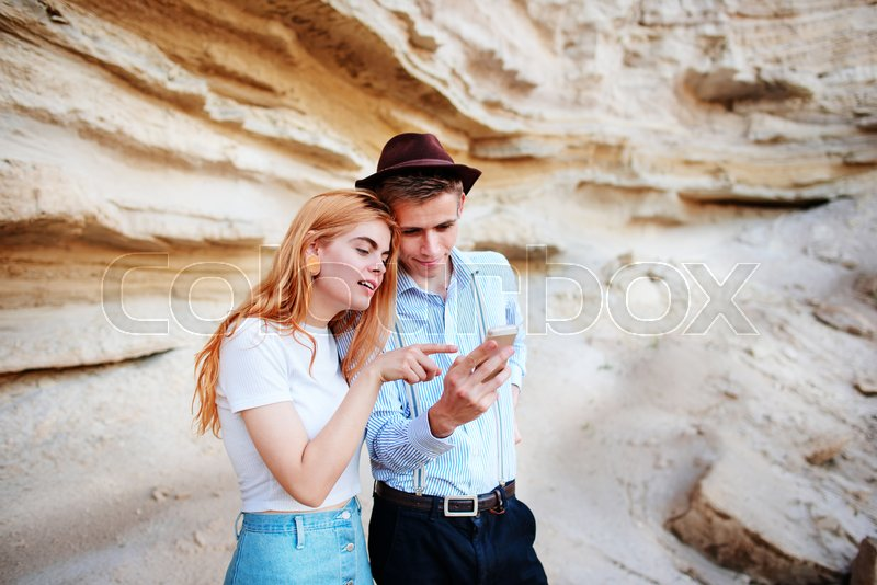 Stock image of 'Attractive man and beautiful woman are looking at the screen of a smartphone on the background of a sand quarry.'