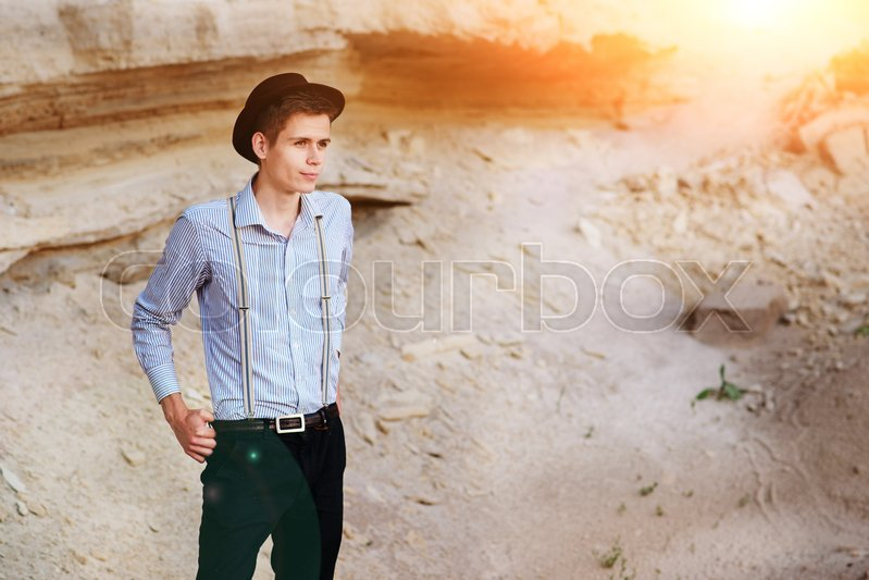 Stock image of 'Stylish attractive man stands in the middle of a sand quarry and poses on the camera.'