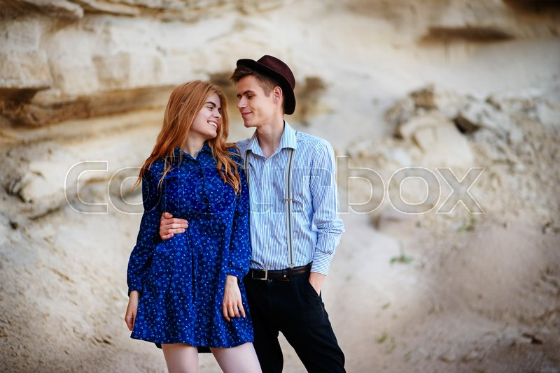Stock image of 'An attractive man hugs a beautiful woman in a blue dress in the middle of a sandy canyon. Lovers are happy, they are smiling to each other.'