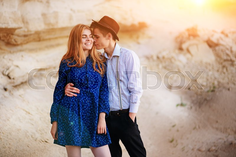 Stock image of 'An attractive man is hugging and kissing an beautiful woman in a blue dress in the middle of a sandy canyon.'
