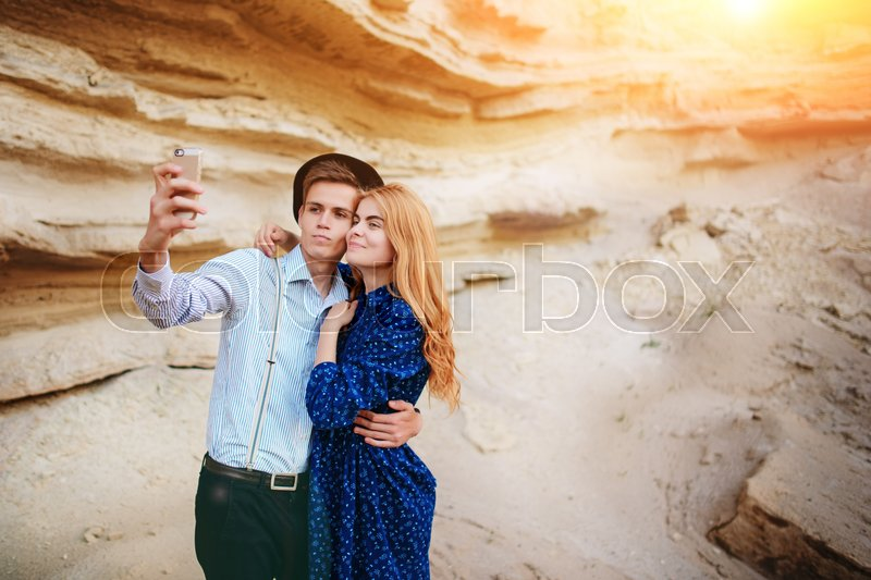 Stock image of 'Attractive man with a beautiful woman are hugging and smiling. They are making selfie on the background of sand quarry.'