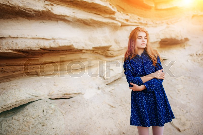 Stock image of 'Beautiful redheaded girl standing in a blue dress in the middle of a sand quarry.'