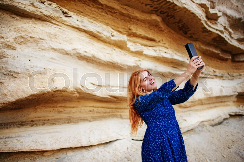 Stock image of 'Beautiful woman smiling and looking at the screen of a tablet and making selfie on the background of a sand quarry.'