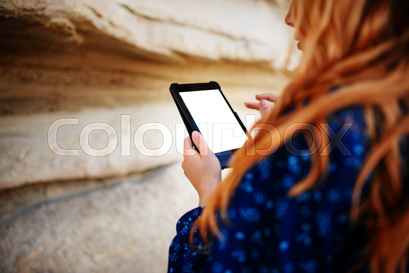 Stock image of 'Woman looking at the screen of a tablet on the background of a sand quarry.'