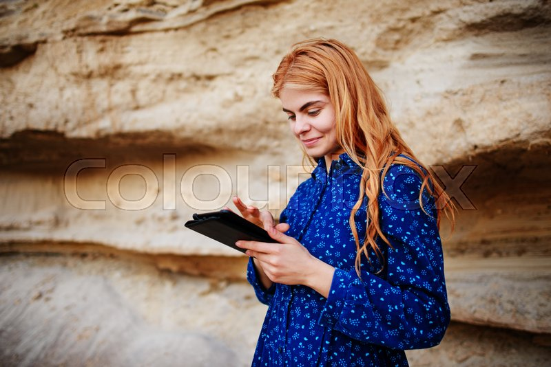 Stock image of 'Beautiful woman smiling and looking at the screen of a tablet on the background of a sand quarry.'