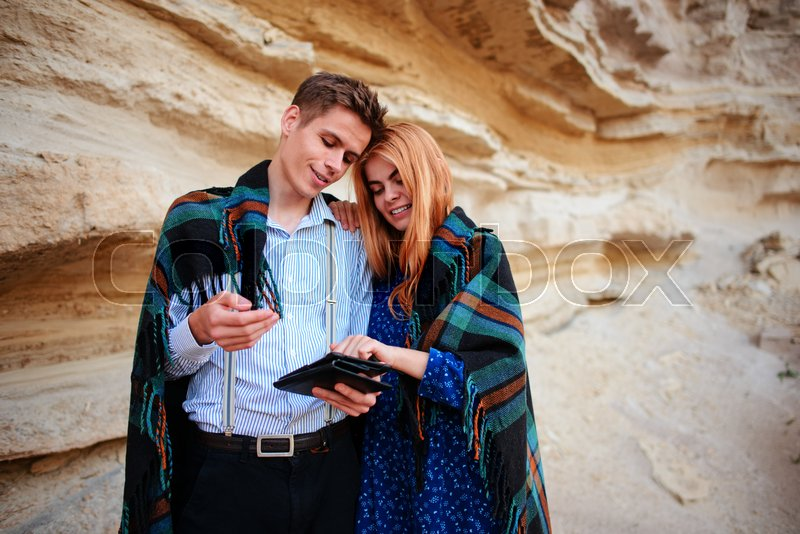 Stock image of 'Beautiful woman and handsome man wrapped in a blanket. They are smiling and looking at the screen of a tablet on the background of a sand quarry.'