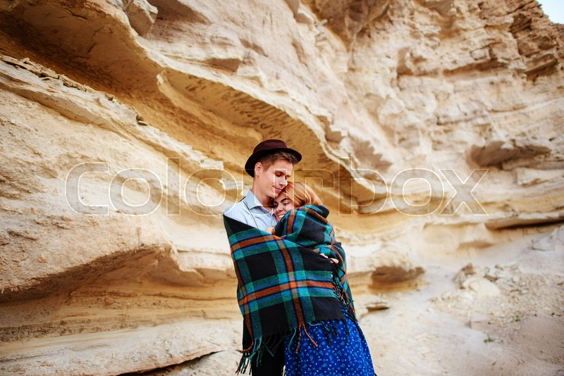 Stock image of 'An attractive man hugs a beautiful woman. The pair wrapped in plaid in the middle of a sandy canyon.'