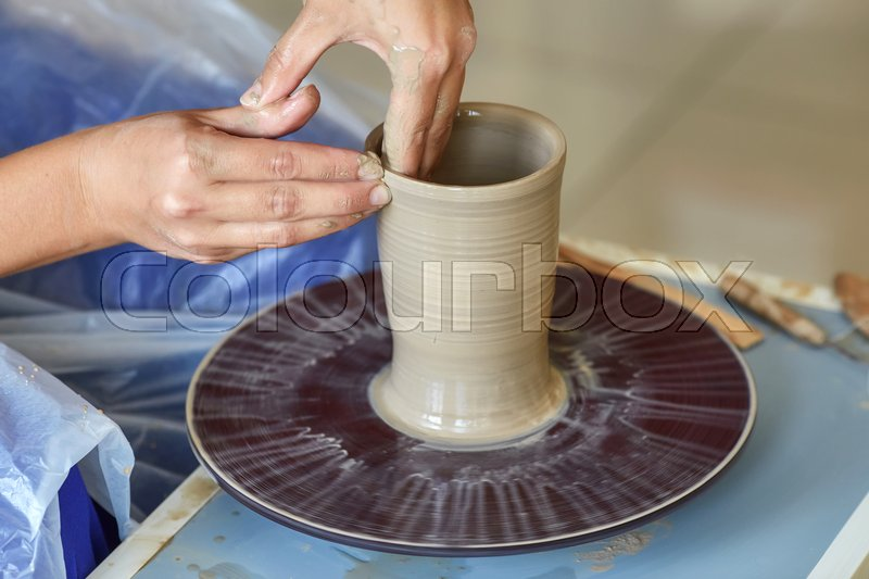Stock image of 'Creating a jar or vase of clay. Woman hands on potter's wheel'