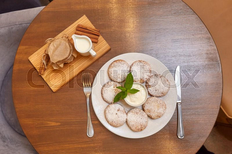 Stock image of 'Cottage cheese curd pancakes or fritters with mint. Traditional Russian and Ukrainian cuisine'