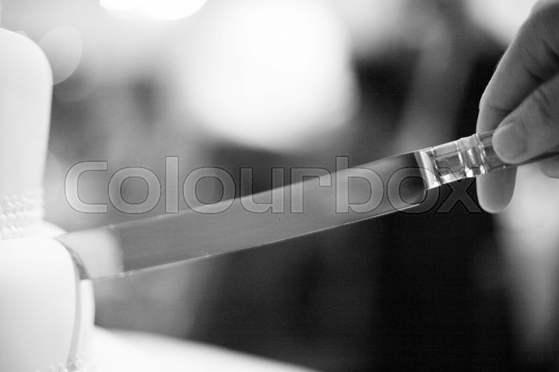Stock image of 'Wedding party evening marriage reception cake cutting ceremony cut with knife.'