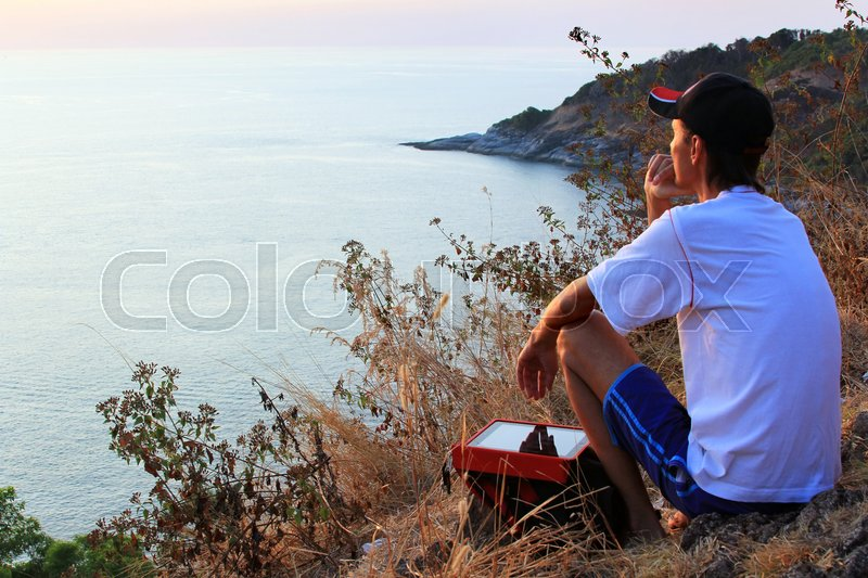 Stock image of 'Lonely man looking with hope at horizon with sunlight during sunset  '