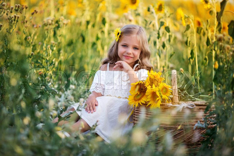 Stock image of 'Pretty child girl is wearing white dress sitting with basket in yellow garden of sunflowers'