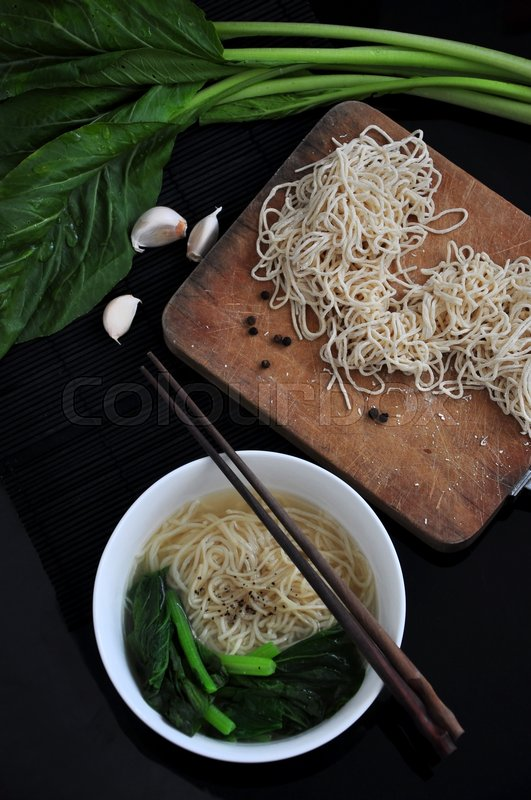 Stock image of 'Top view of clear soup noodle bowl with ingredients on black background'