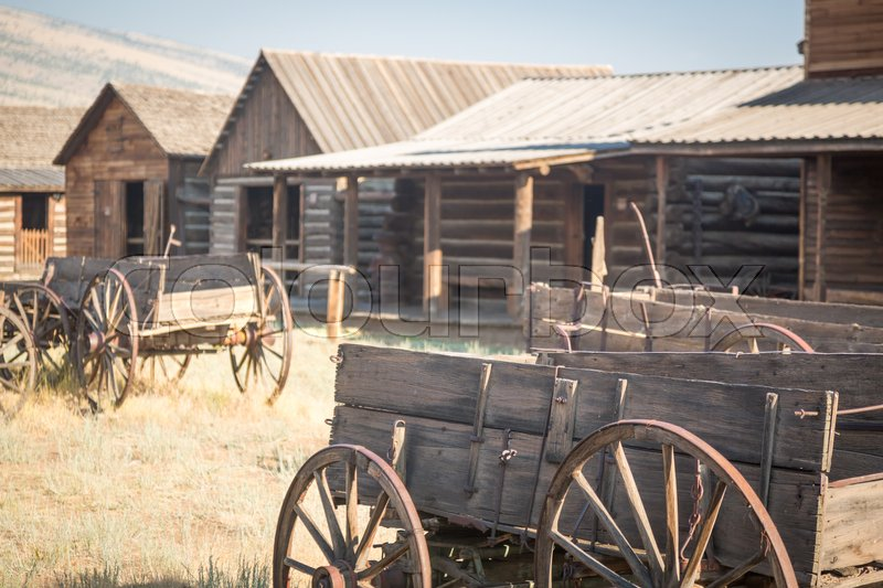 Stock image of 'Abstract of Vintage Antique Wood Wagon and Log Cabins.'