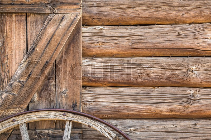 Stock image of 'Abstract of Vintage Antique Log Cabin Wall and Wagon Wheel.'