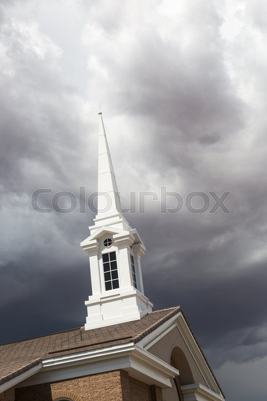 Stock image of 'Church Steeple Tower Below Ominous Stormy Thunderstorm Clouds.'