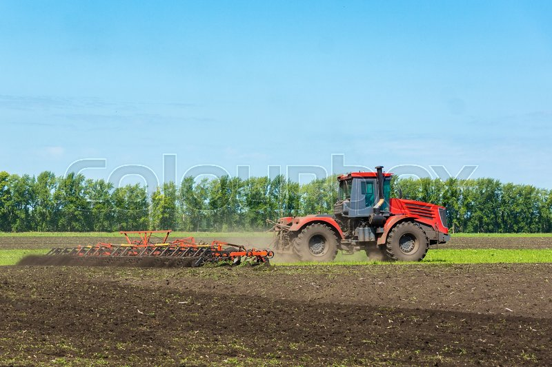 Stock image of 'Tractor on the field plows the land, Russia, village, summer'
