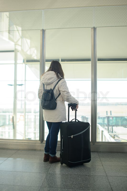 Stock image of 'Girl with a suitcase in the airport waiting room. Young passenger looks through a large window on the runway.'