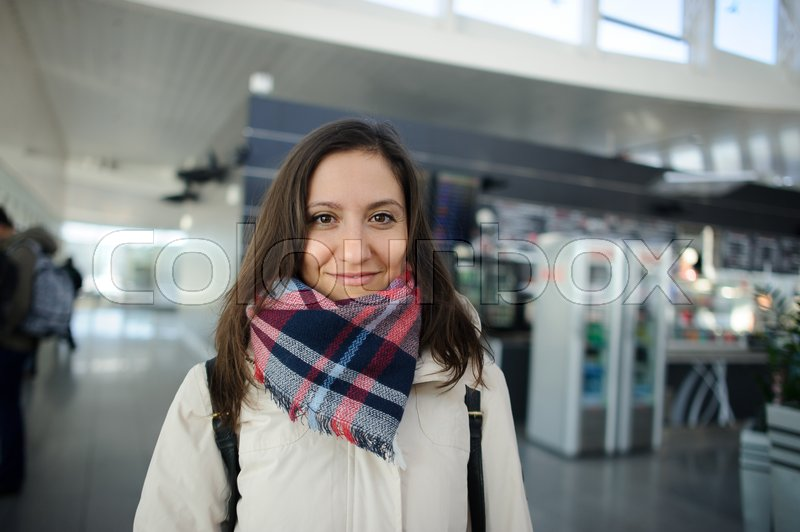 Stock image of 'Young woman in the airport waiting room. She smiles. Modern building. Comfort for the passengers.'