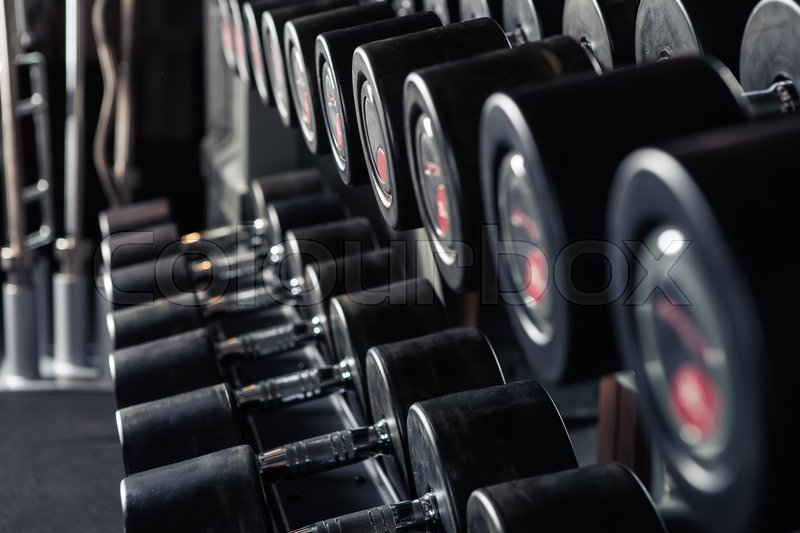 Stock image of 'Sports dumbbells in modern sports club. Weight Training Equipment'