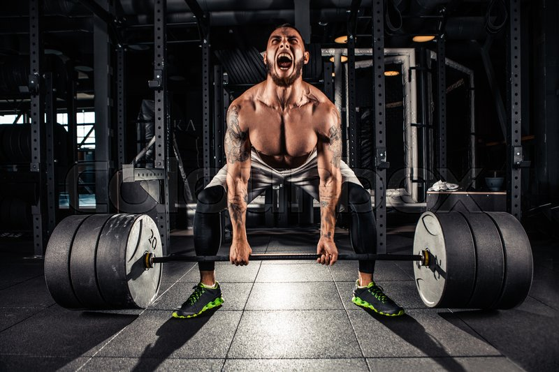 Stock image of 'Muscular men lifting deadlift In the gym'