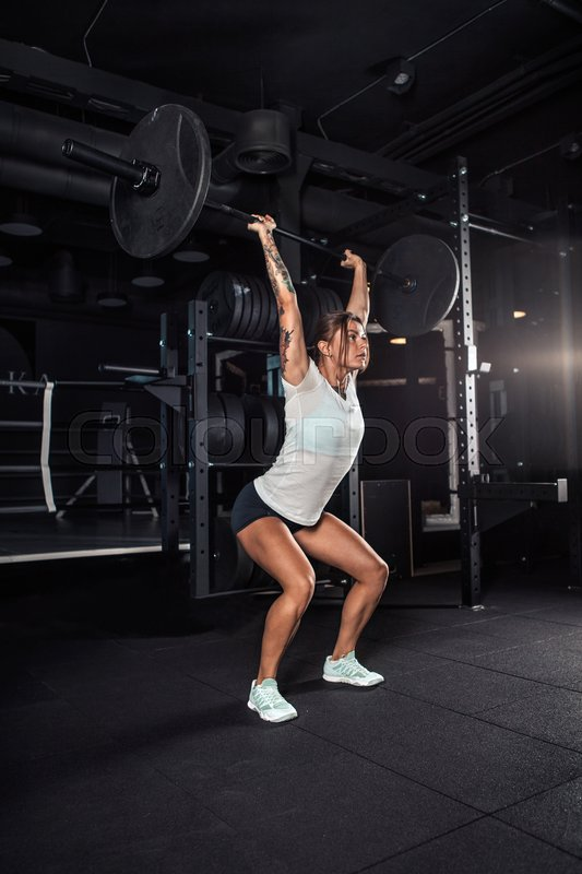 Stock image of 'Attractive young athlete with muscular body exercising crossfit. Woman in sportswear doing crossfit workout'