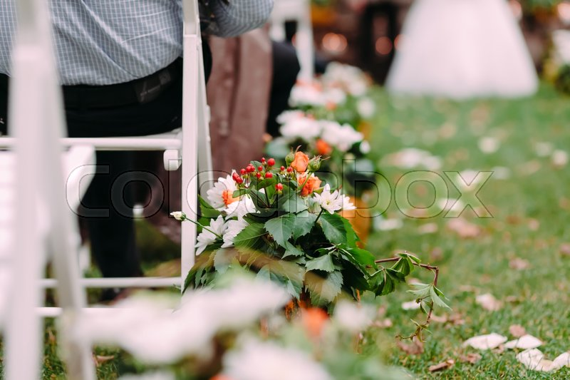 Stock image of 'Decorations of white and orange flowers with green leaves decorations during outdoor wedding ceremony'