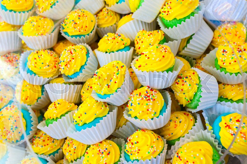 Stock image of 'Pile of colorful homemade cakes in paper baskets with yellow cream'