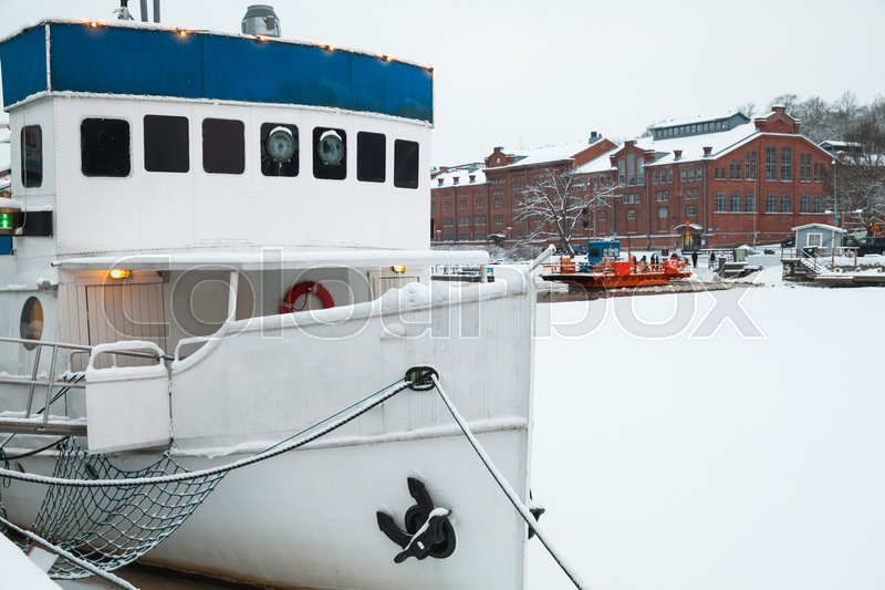 Stock image of 'Small boat is moored near river coast. Winter in Turku town, Finland'